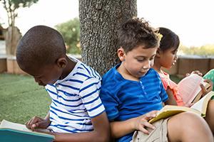 Kids reading around a tress